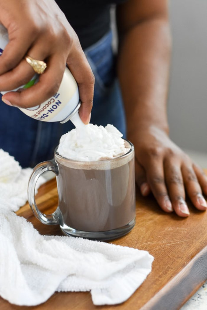 adding dollop of non-dairy whipped topping to vegan hot chocolate