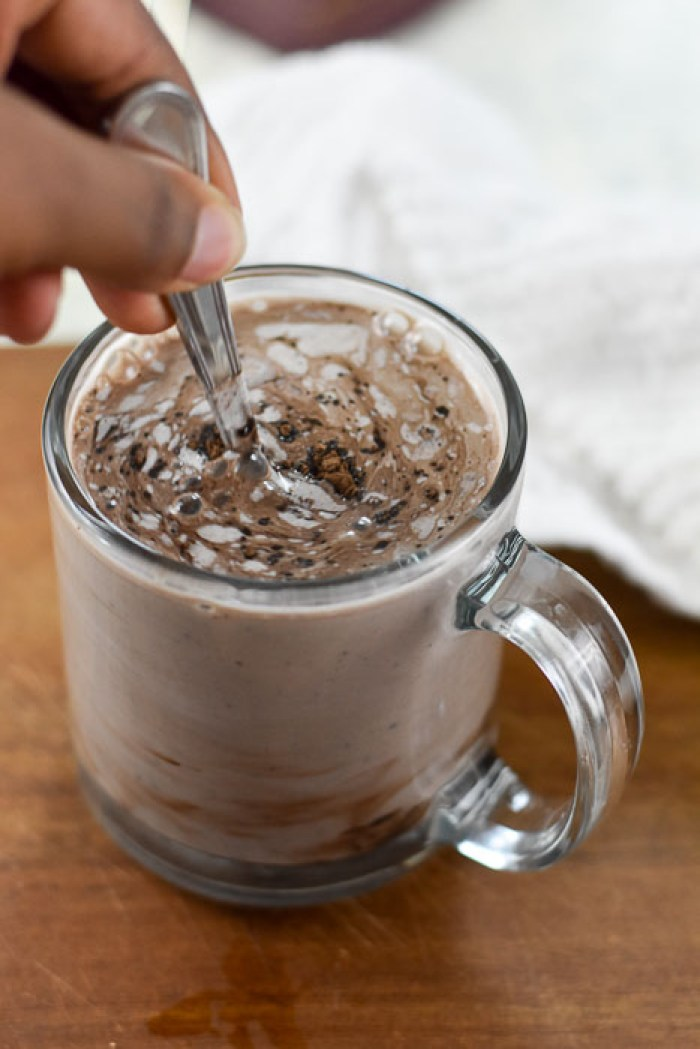 stirring mug of vegan hot cocoa