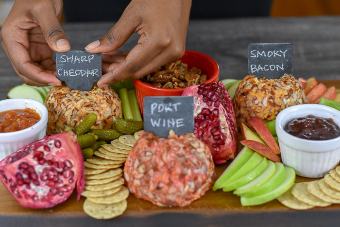 adding slate sign to cheese ball on cheese board