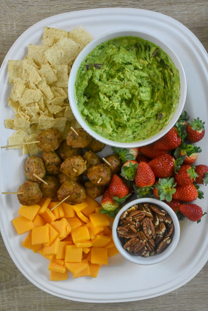 tray of appetizers with guacamole, tortilla chips, meatballs, strawberries, cheddar, and nuts