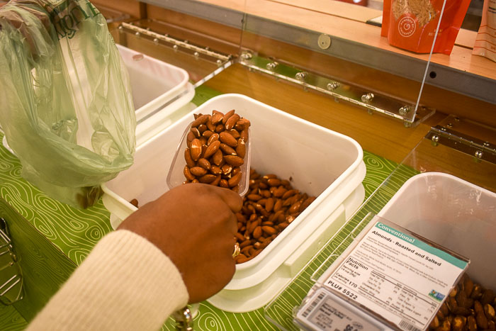 scooping almonds out of bulk bucket