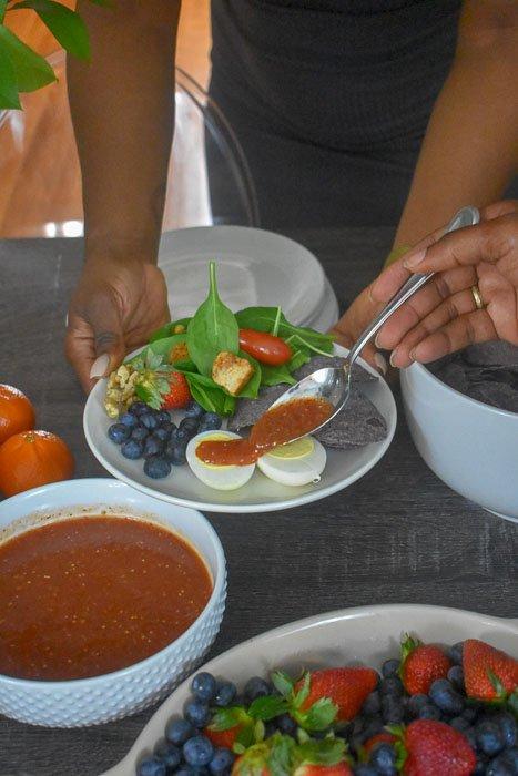 spooning salsa rojo onto hard-boiled eggs