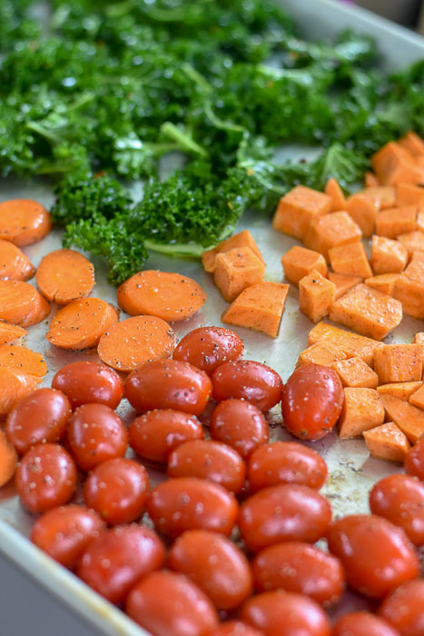 tomatoes, carrots, sweet potatoes, and kale on sheet pan