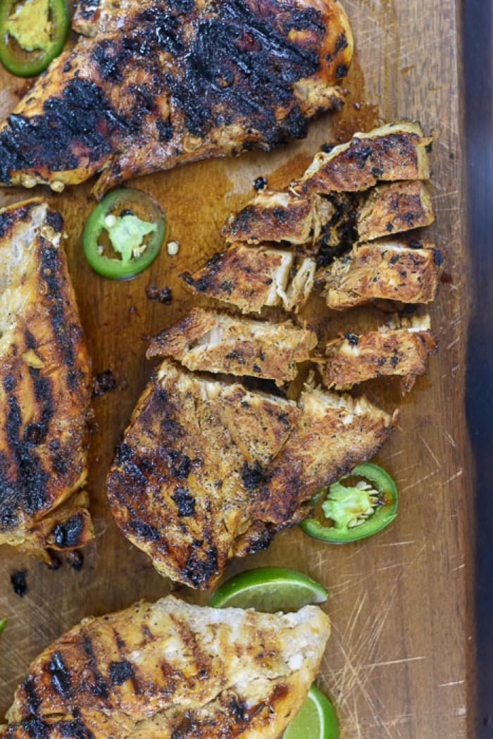grilled chicken sliced on wooden cutting board