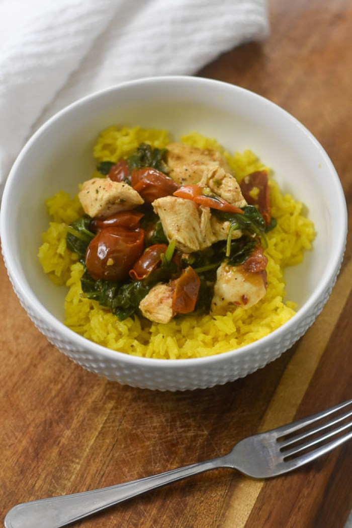 sauteed chicken and vegetables over saffron yellow rice