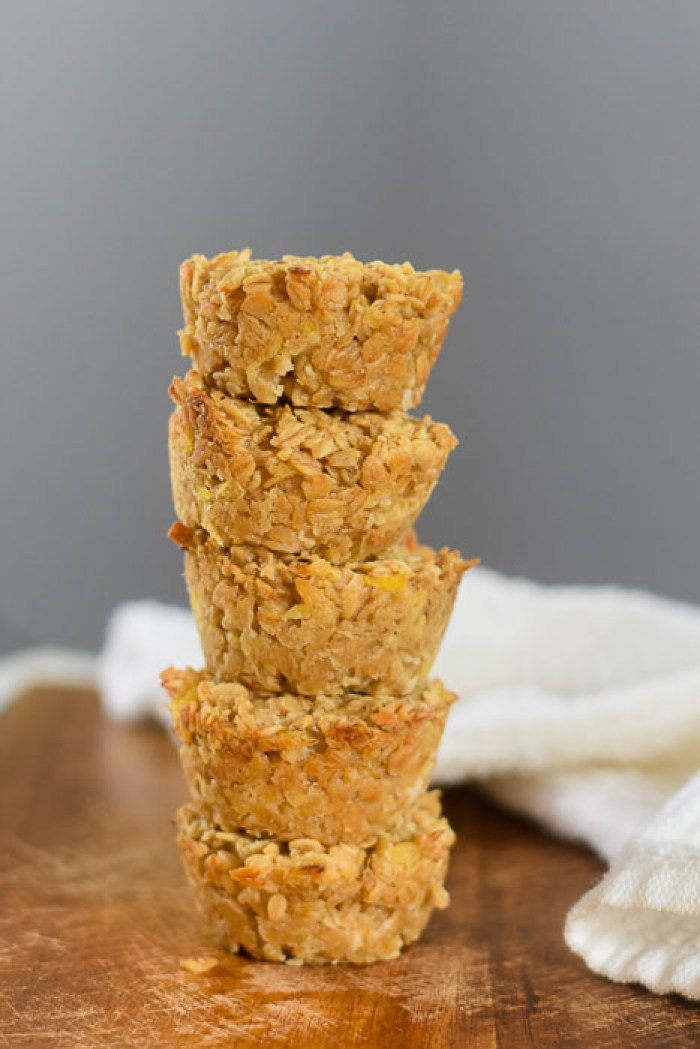 stacked pina colada oatmeal breakfast muffins on wooden cutting board