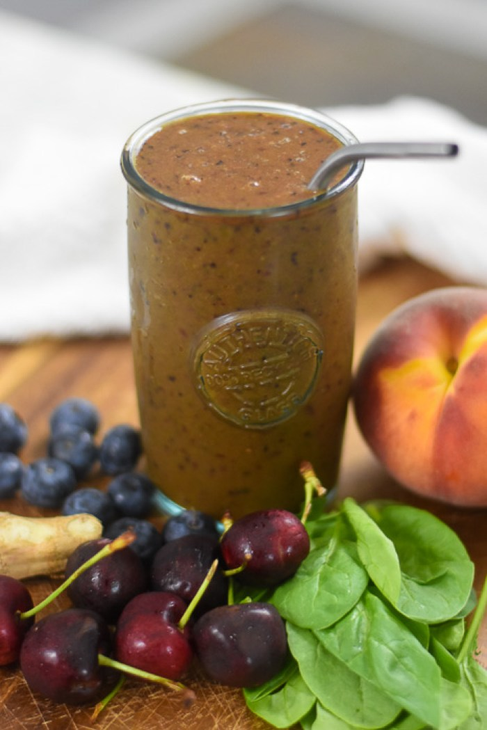 fresh fruit smoothie surrounded by cherries, blueberries, ginger, spinach leaves, and peach