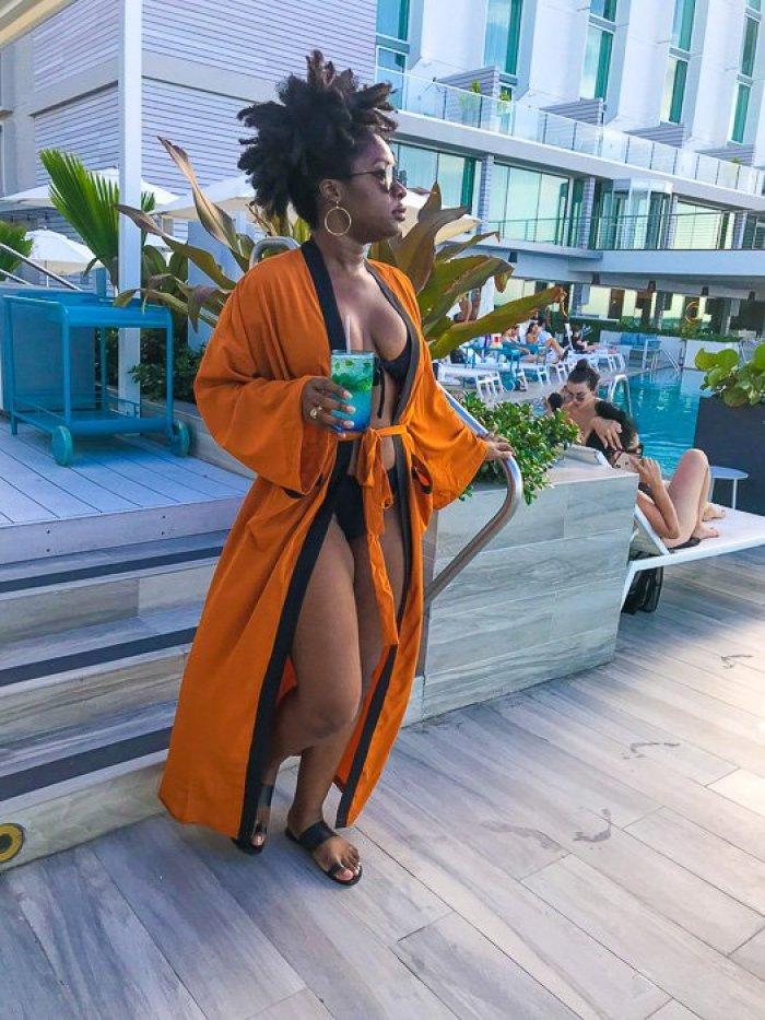 Dash of Jazz wearing orange kimono coverup at Serafina Beach Hotel pool