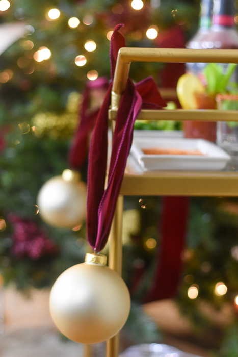 gold Christmas ornaments adorning a bar cart
