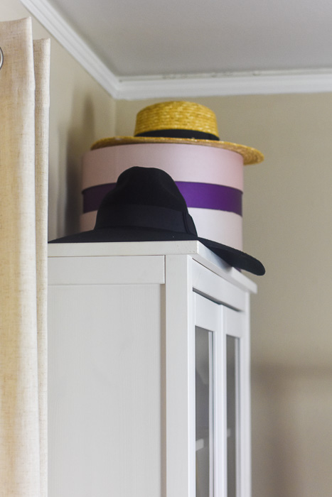 hats and hatboxes styled on bookshelf