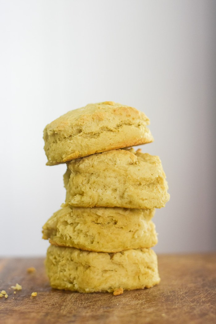 stack of four vegan buttermilk biscuits on wooden cutting board.