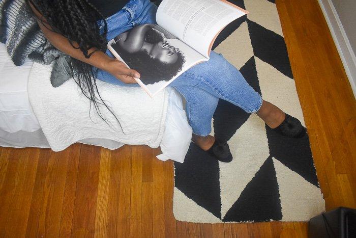 sitting on bed reading Radiant Magazine