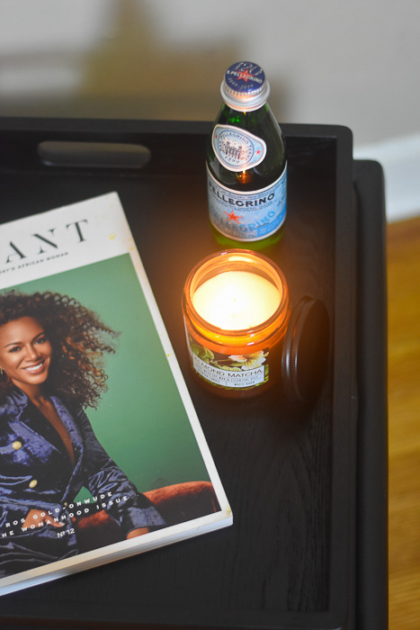 tray with candle, magazine, and bottle of water