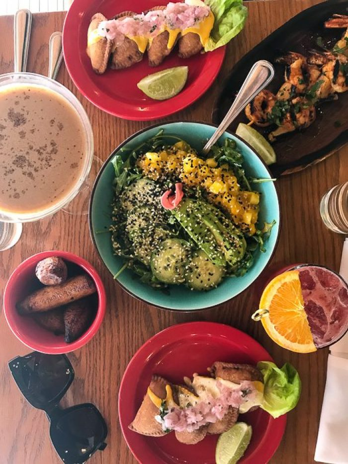 spread of salad, cocktails, and tapas at Baby BRASA in NYC