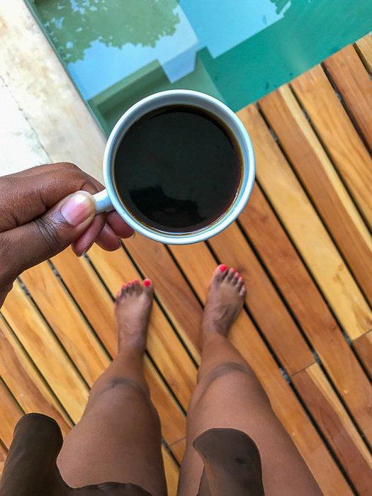 holding mug of black coffee on pool deck