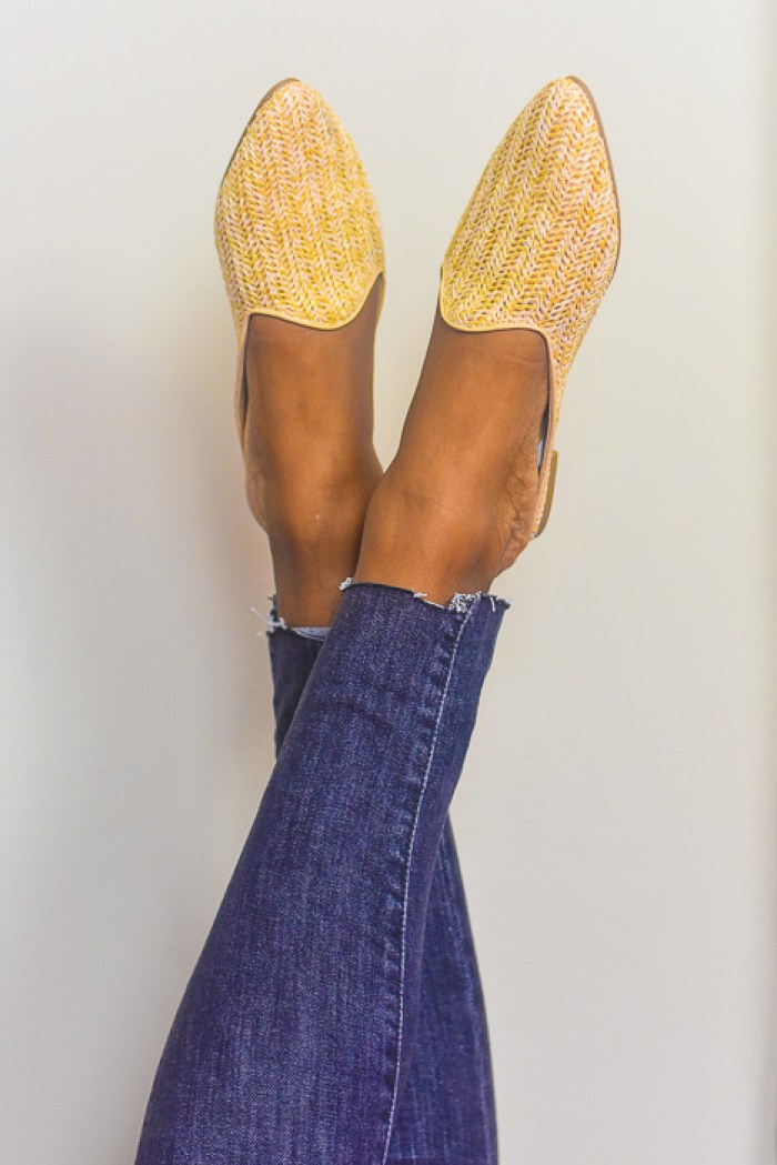 feet up against wall wearing straw mules