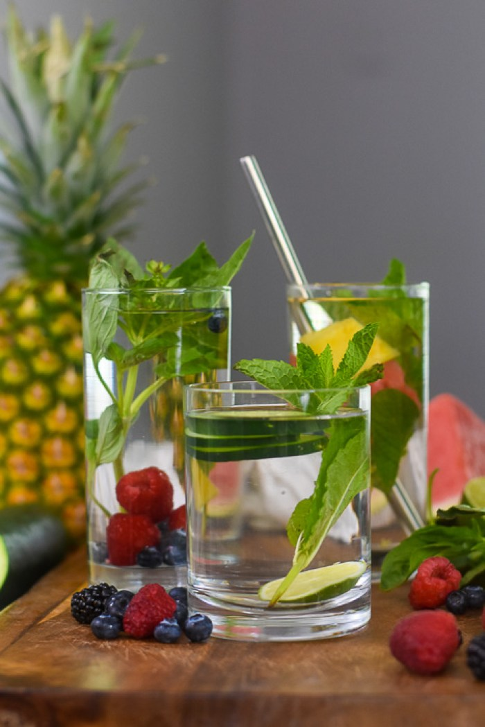 three glasses of infused water surrounded by fresh fruits