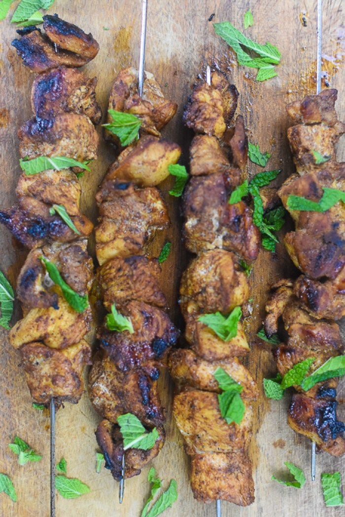 Moroccan-spiced grilled chicken skewers garnished with mint