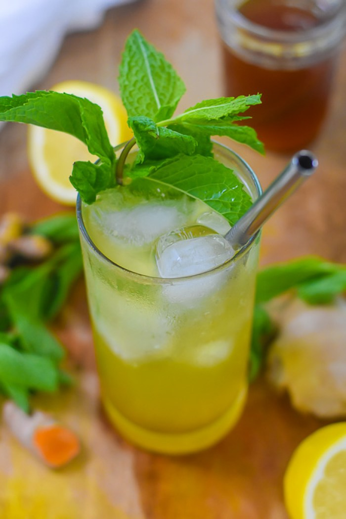 highball glass of sparkling turmeric gingerade with mint garnish