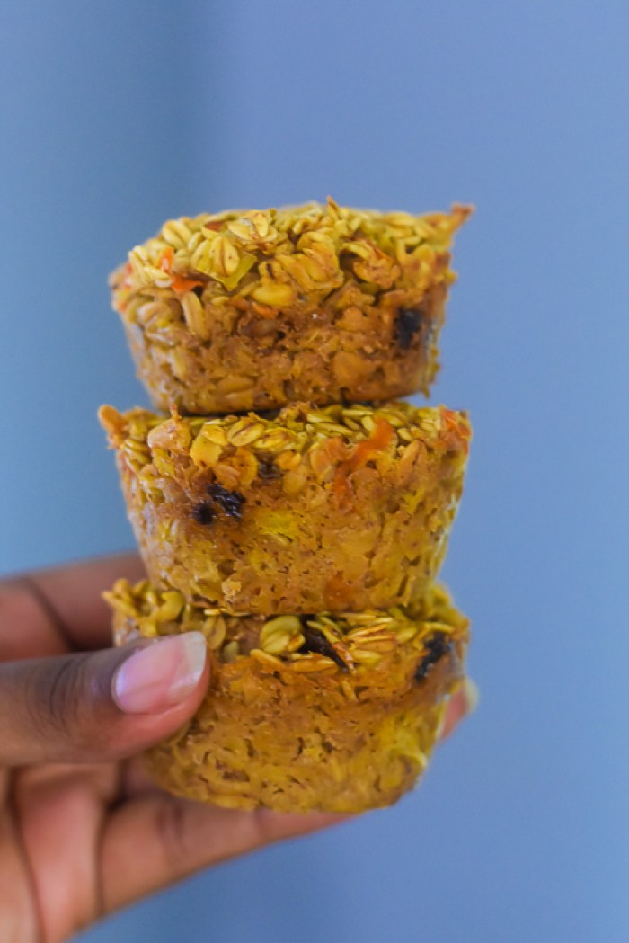 holding three carrot cake oatmeal breakfast muffins