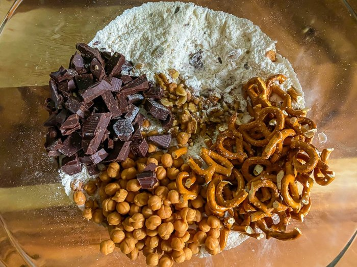 caramel bits, pretzel pieces, chocolate pieces, and chopped walnuts in bowl of flour mixture