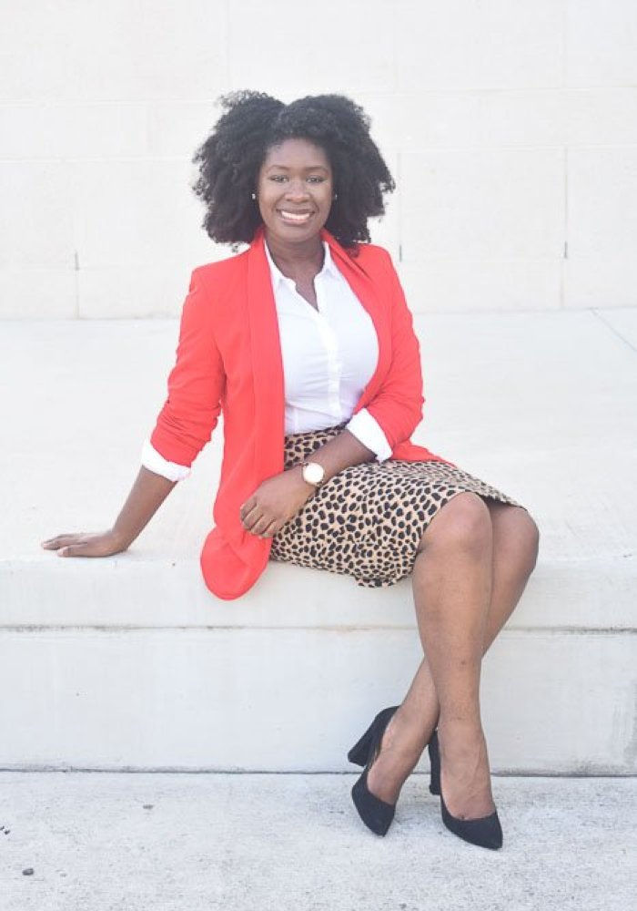 Jazzmine seated outdoors, wearing bright red blazer and leopard print skirt