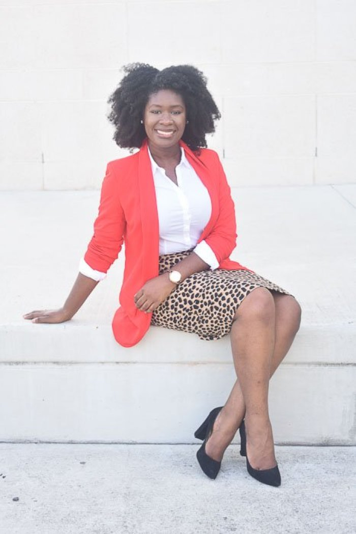 Jazzmine seated outdoors, wearing natural afro hair with a business professional outfit.