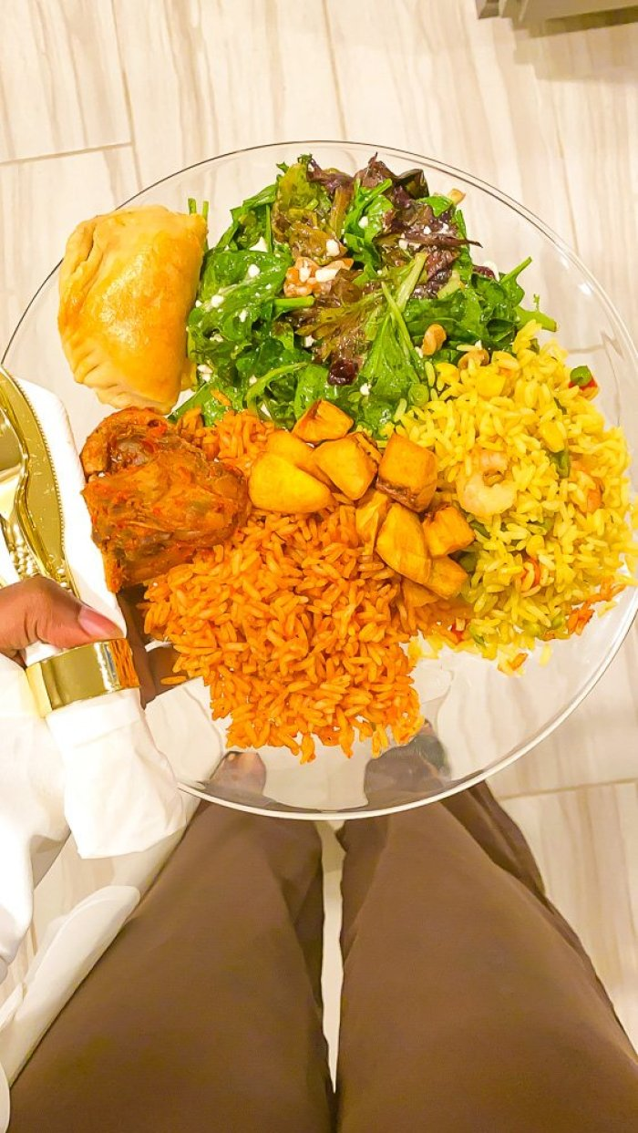 holding plate of salad, rice, beef, and fried plantain