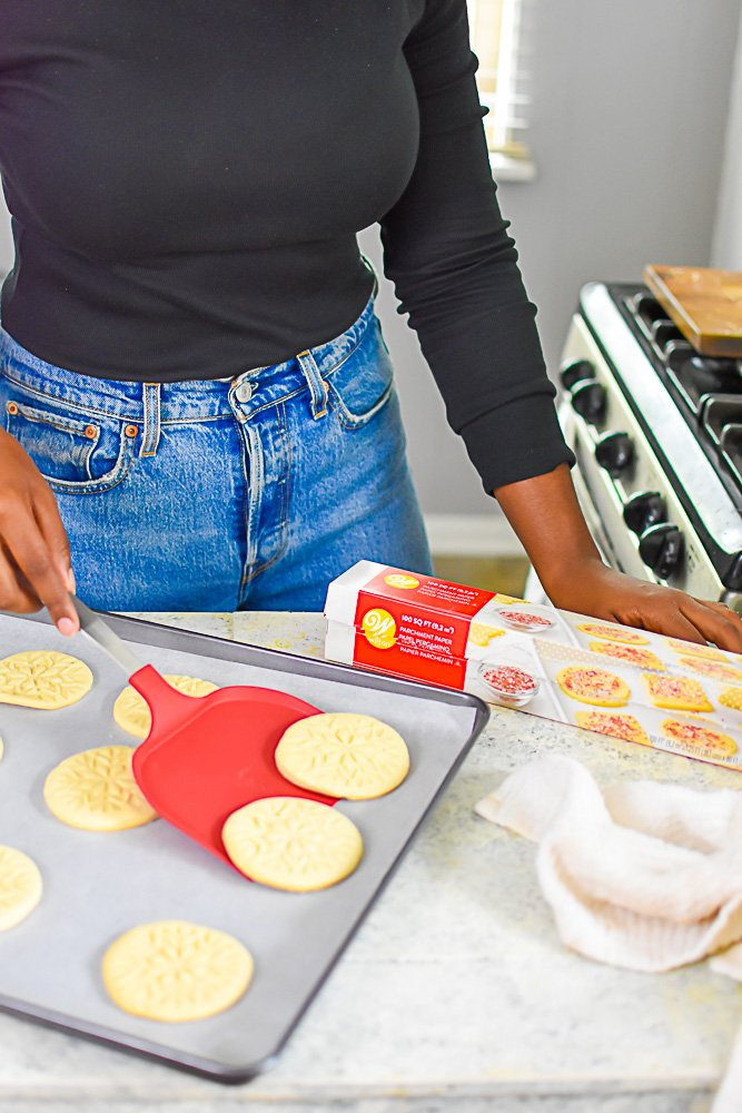 scooping sugar cookies off baking sheet with large spatula