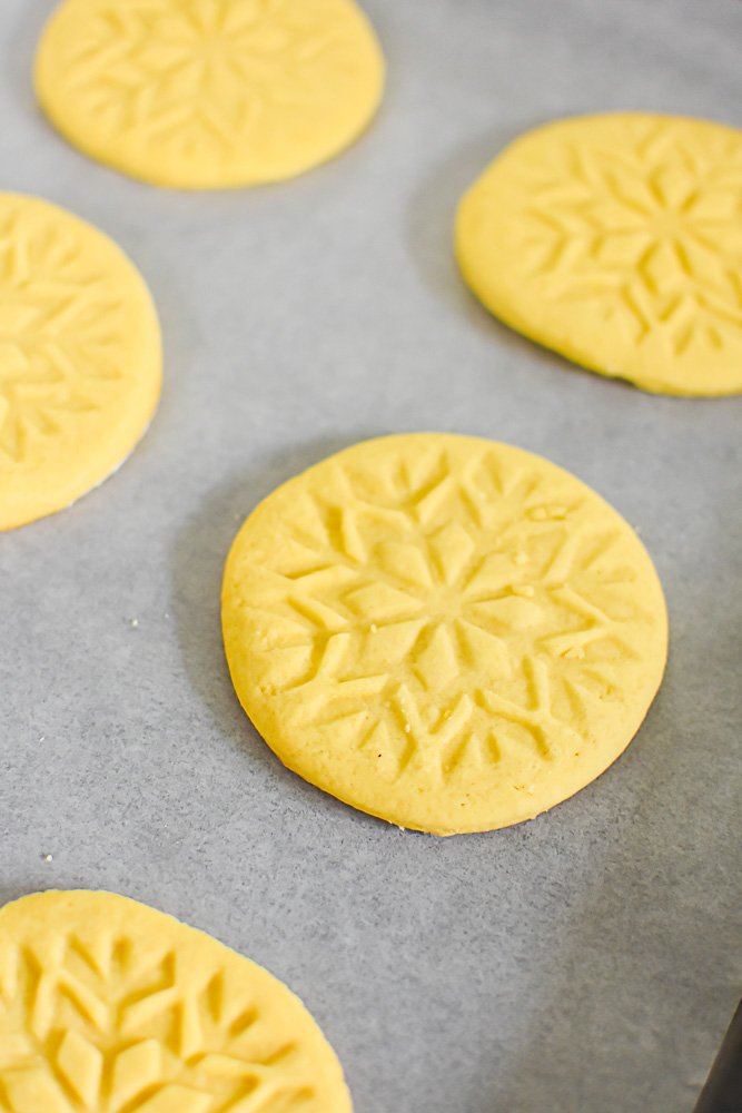 stamped sugar cookies on parchment-lined cookie sheet