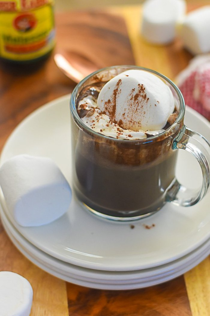 mug of bourbon gingerbread hot cocoa on stack of white plates