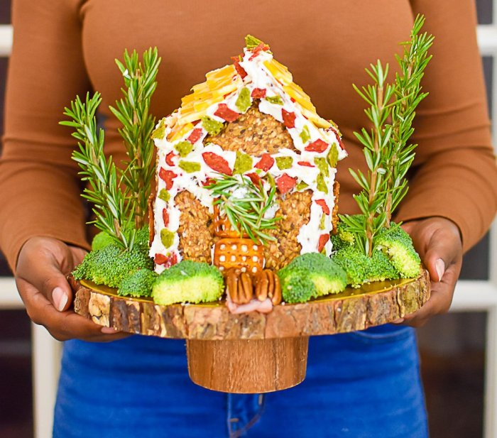 holding finished charcuterie chalet on wooden cake stand
