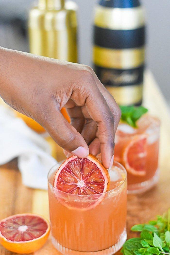 placing blood orange slice into rocks glass with bourbon cocktail