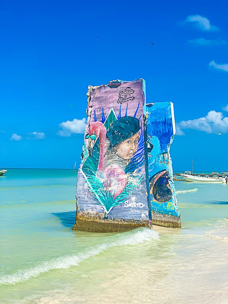 murals painted on large stones at beach shoreline