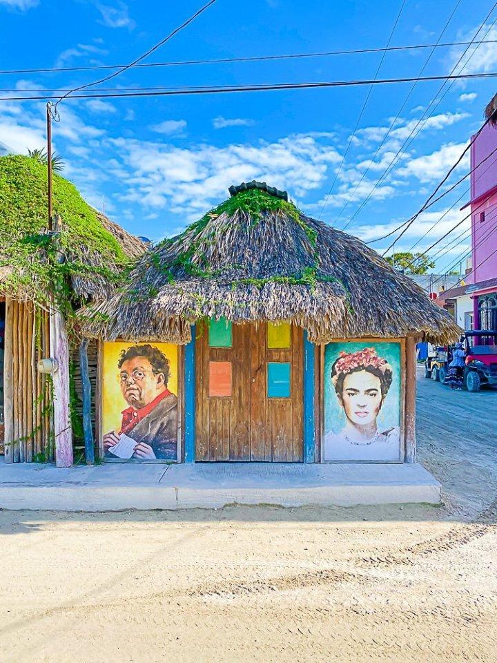 murals painted on doors of grass-roof building