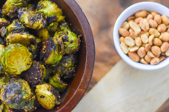 bowl of roasted brussles sprouts next to smalller bowl of groundnut (roasted peanuts).
