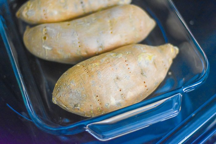 sweet potatoes prepared for roasting in glass pan.