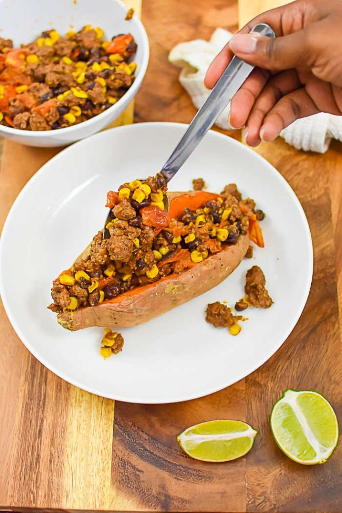 filling baked sweet potato with taco filling.