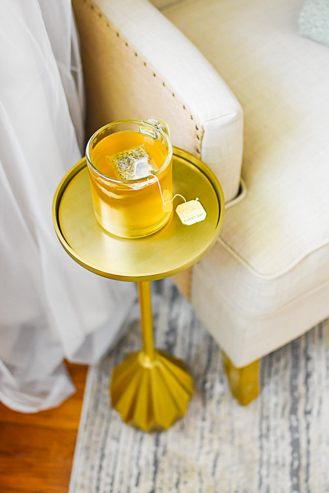 brass drink table with clear mug of tea sitting on top.