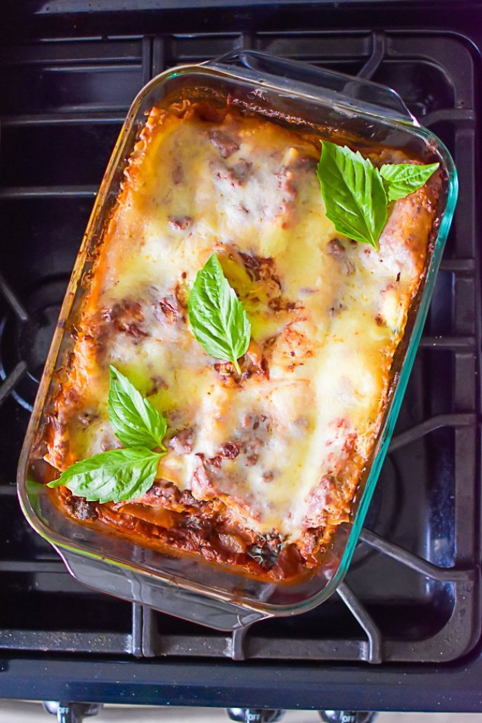 baked pan of lasagna with red wine sauce on stove top, garnished with fresh basil leaves.