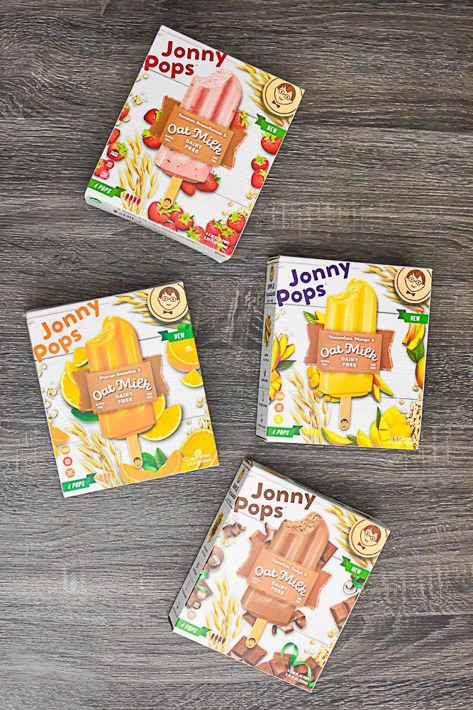 box of four JonnyPop flavors on wood grain table top.