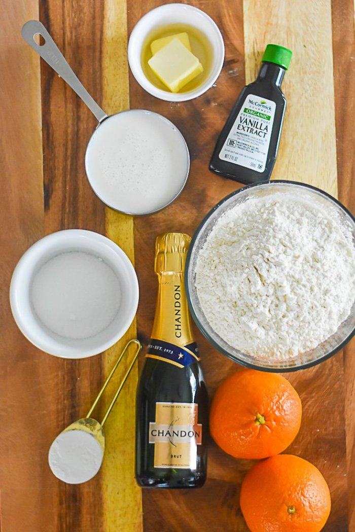two oranges, mini bottle of champagne, spoonful of baking powder, bowl of flour, ramekin of sugar, bottle of vanilla extract, two pats of butter, and measuring cup of milk on countertop.