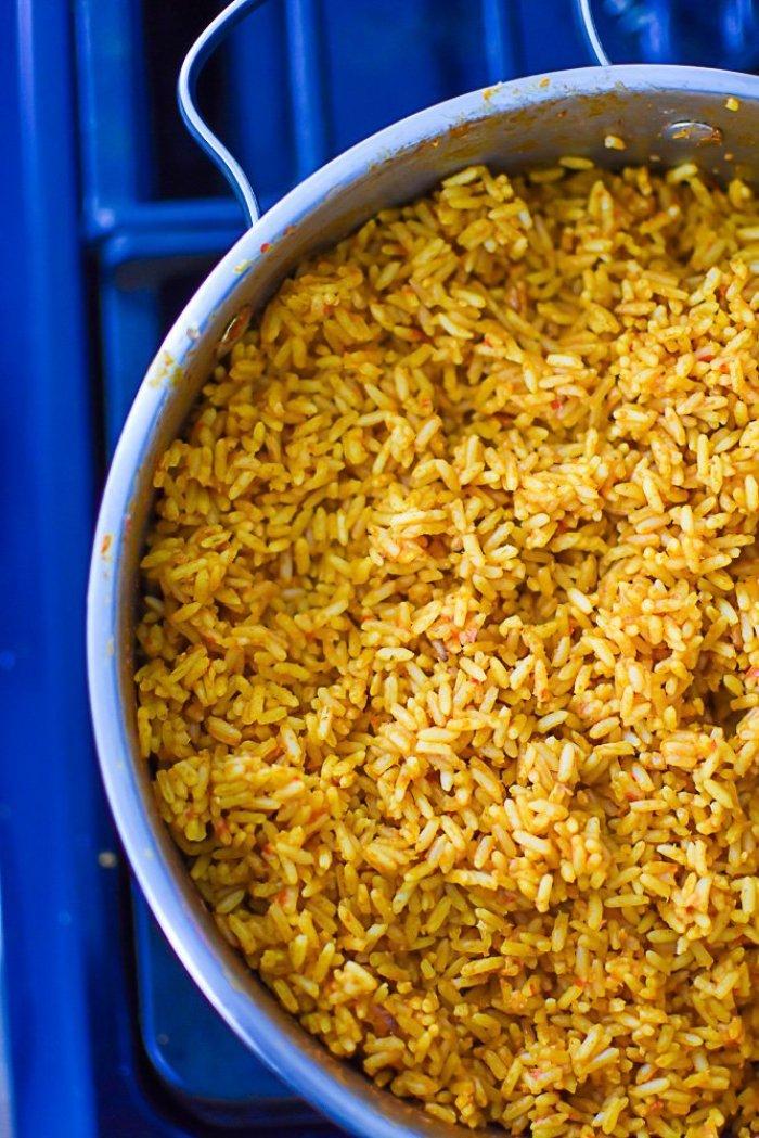 cooked Nigerian jollof rice in silver pot.