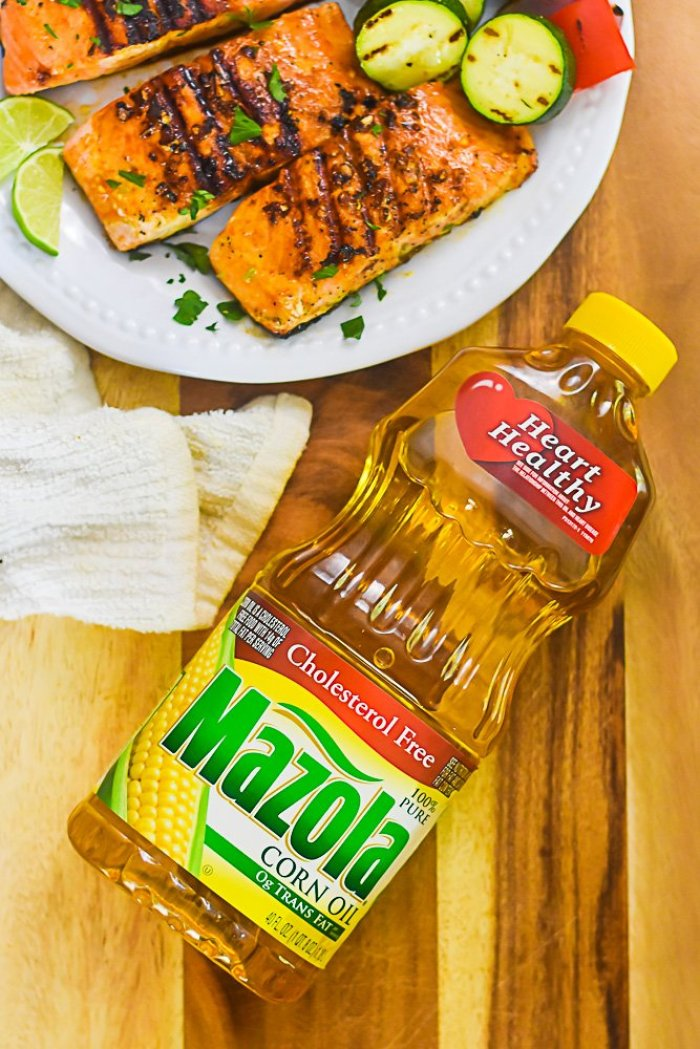bottle of Mazola Corn Oil laying next to platter of grilled salmon filets.
