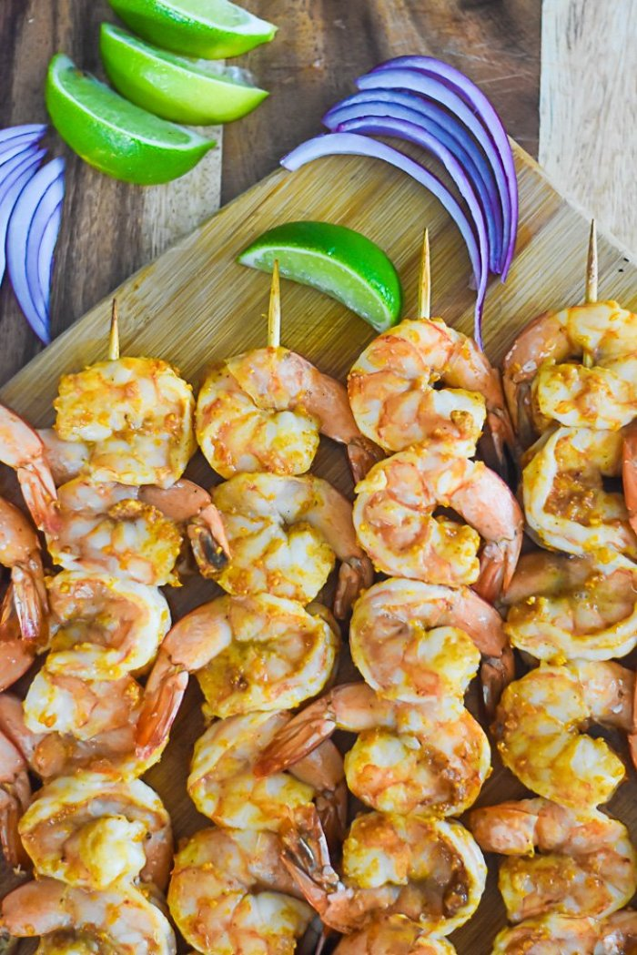 skewers of suya shrimp with slices of red onion and wedges of lime.