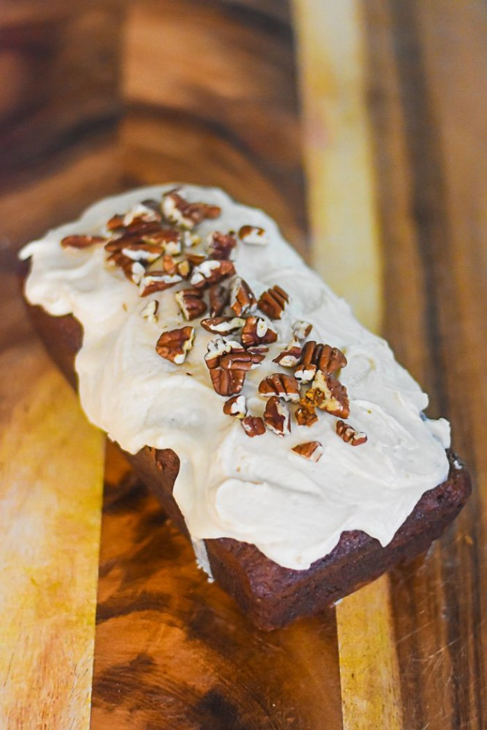 carrot cake loaf frosted with praline cream cheese frosting and garnished with chopped pecans.