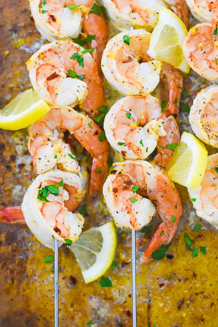 broiled lemon pepper shrimp on metal skewers garnished with pieces of fresh lemon.
