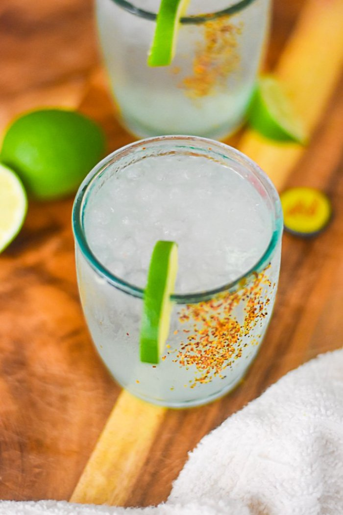 recycled rocks glass full of mezcal ranch water with a lime slice garnish and tajin seasoning on the side of the glass.