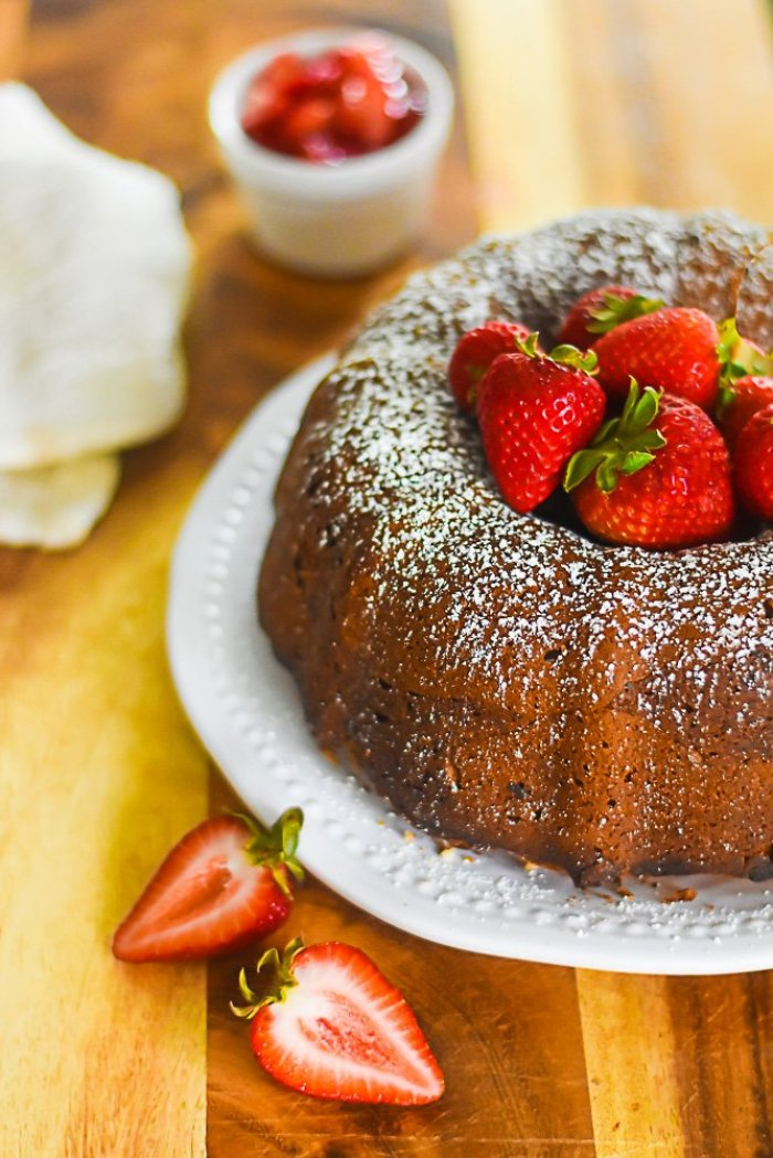 baked sour cream strawberry pound cake decorated with powdered sugar and pile of fresh strawberries.