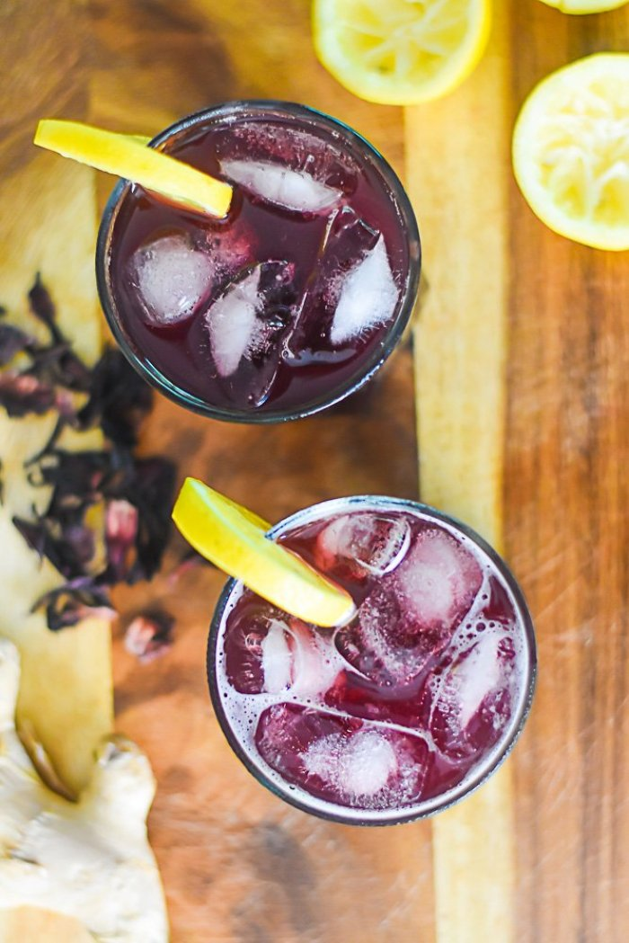 two glasses of zobo lemonade with lemon slice garnishes on a wooden countertop.